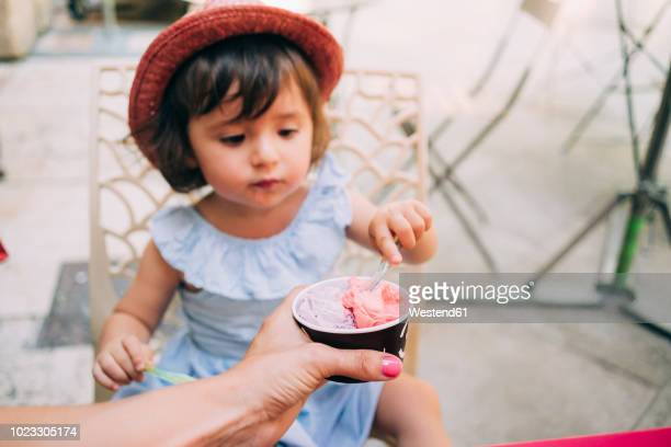 cute toddler girl eating an ice cream held by her mother - premier plan net photos et images de collection