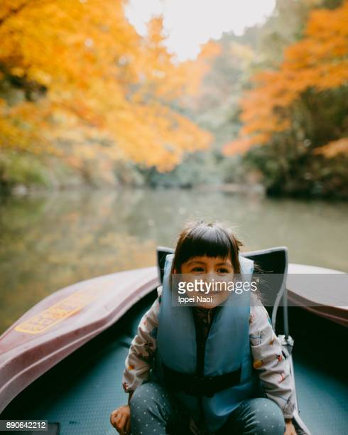 Cute toddler girl enjoying a boat ride with autumn foliage