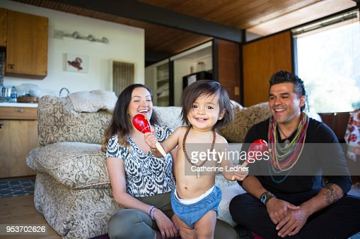 Cute toddler girl holding shakers with laughing parents in background
