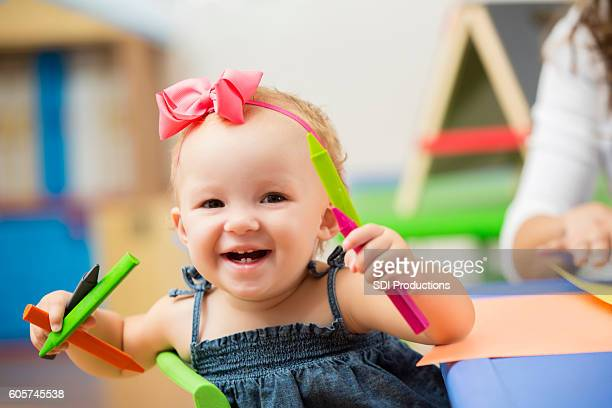 Cute toddler girl in preschool smiling and playing with crayons