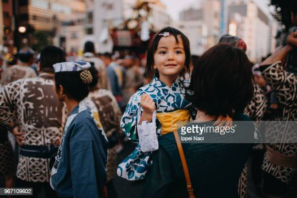 cute toddler girl in yukata carried by mother at traditional japanese festival - 伝統的な祭り ストックフォトと画像