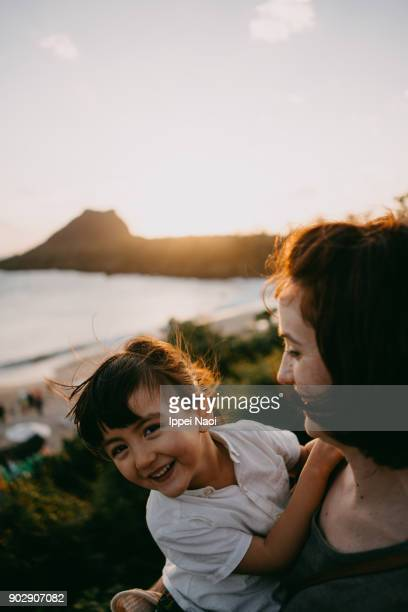 Cute toddler girl laughing with her mother at sunset