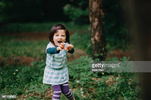 Cute toddler girl making a monster face in forest