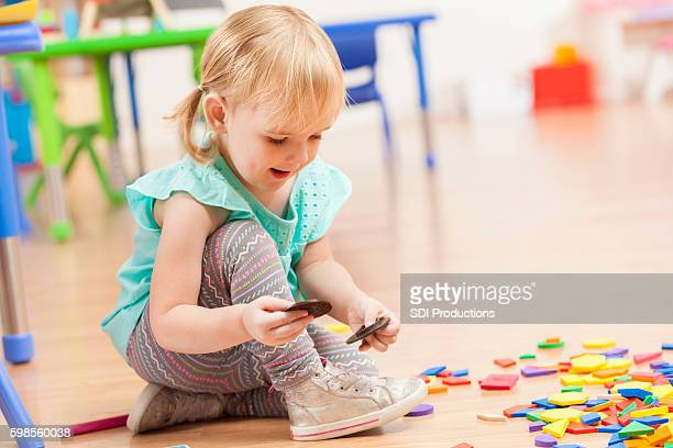 Cute toddler girl playing with toys on daycare floor