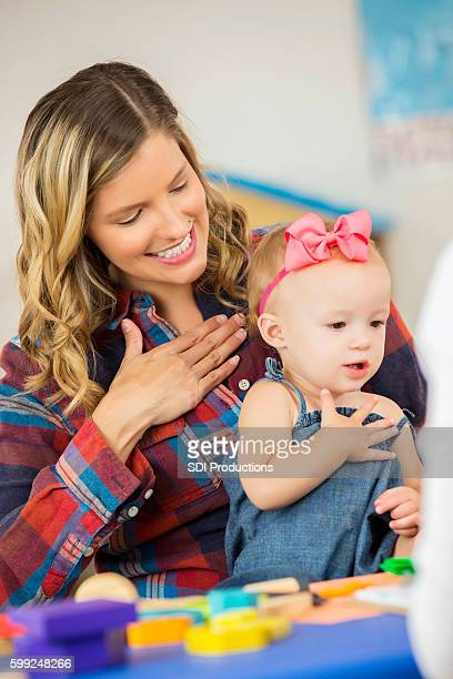 Cute toddler girl practicing sign language with her mother