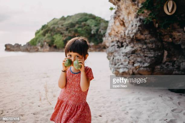 cute toddler girl smelling guavas and smiling at camera on beach - 鹿児島県 ストックフォトと画像