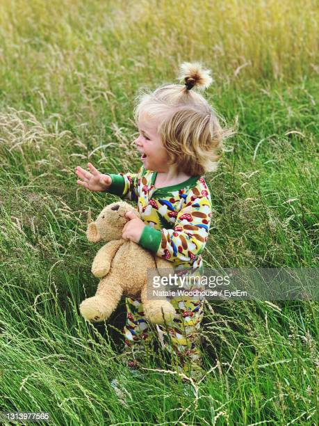 cute toddler playing in long grass with his teddy - one baby boy only stock pictures, royalty-free photos & images