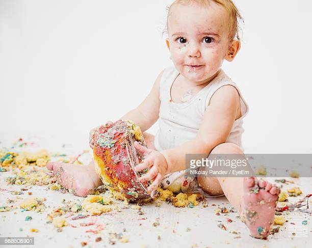 Cute Toddler Playing With Cake Over White Background