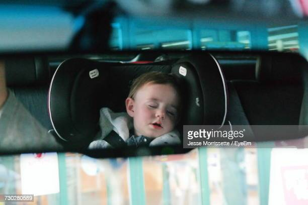 Cute Toddler Sleeping Seen Through Rear View Mirror Of Car