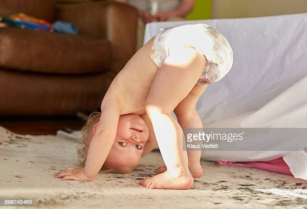cute toddler standing on head and smiling - windel stock-fotos und bilder
