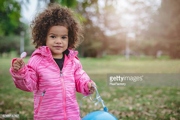 cute toddler with afro hair, holding lollipop - black jacket stock pictures, royalty-free photos & images