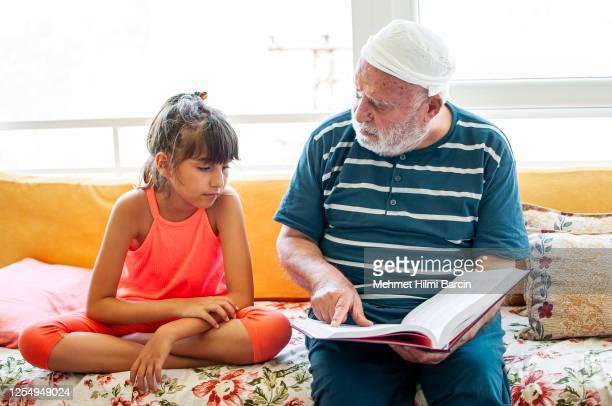 ein süßes türkisches mädchen mit großvater zu hause, lesen buch - enzyklopädie stock-fotos und bilder