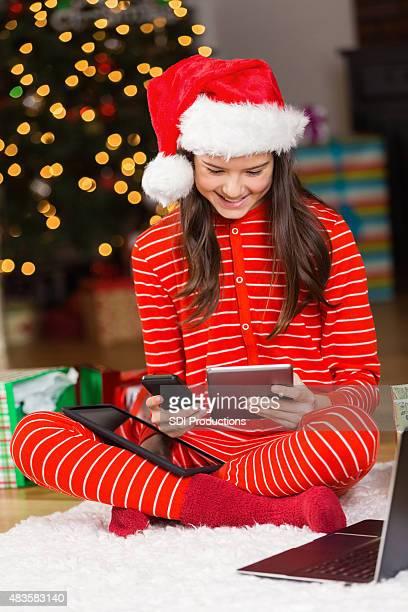 Cute tween girl holding electronic Christmas gifts