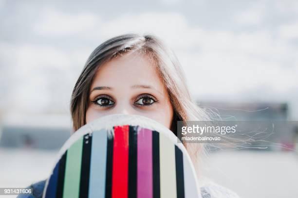 Jolie fille urbaine maintenant skateboard en skatepark