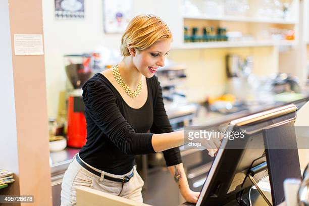Cute waitress working with cash register,typing on monitor