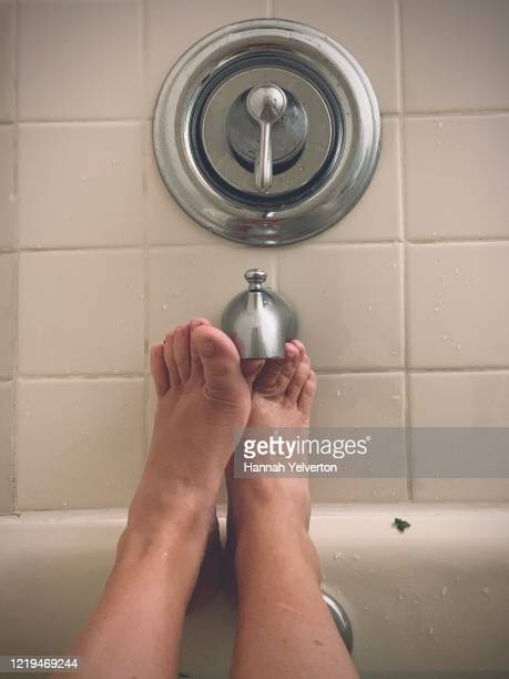 cute well groomed women's feet in bathtub - massage tantrique photos et images de collection