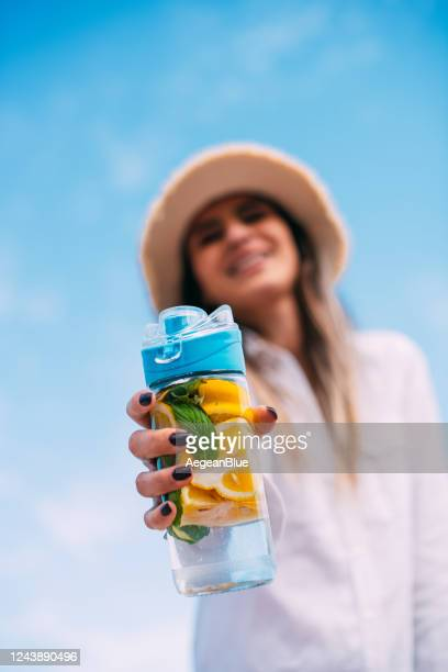 cute woman drinking detox water - infused water stock pictures, royalty-free photos & images