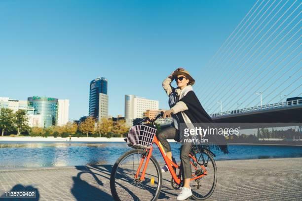 linda mujer explorando valencia en bicicleta - valencia fotografías e imágenes de stock