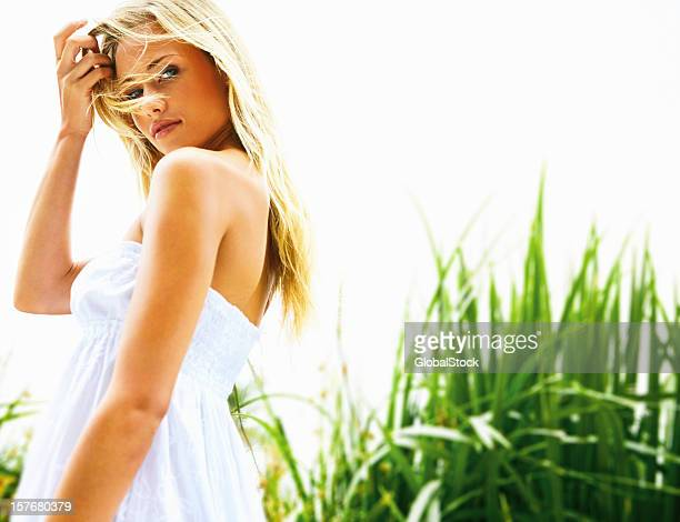 Cute woman in white dress against a natural background