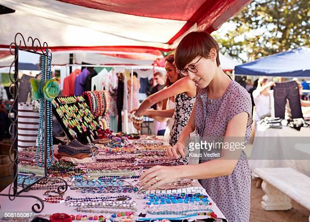 cute woman looking at necklaces at market - bancarella foto e immagini stock
