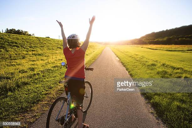Cute Woman Riding Her Bike Down Sunlit Trail- Arms Raised