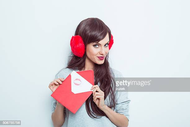 0c3c13af45 Cute woman wearing earmuffs holding love letter