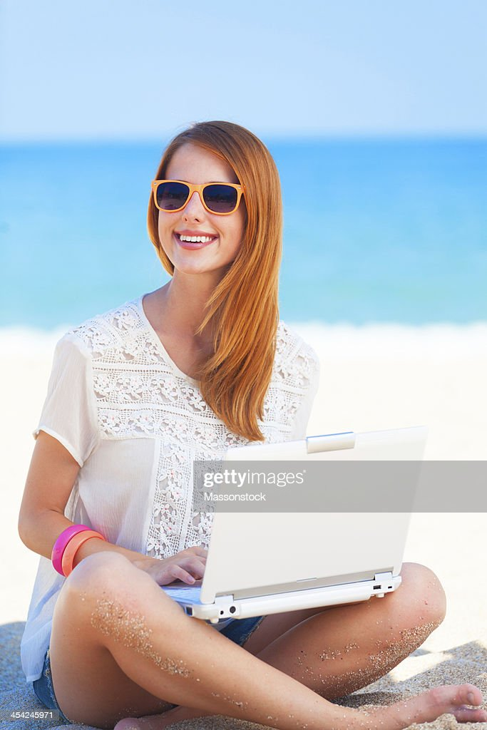 Cute woman with white laptop on the summer beach : Stock Photo