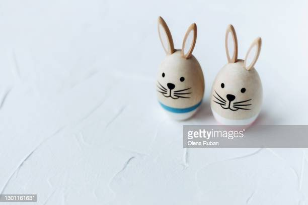 cute wooden rabbits with pink and blue stripes on a white background - april stock pictures, royalty-free photos & images