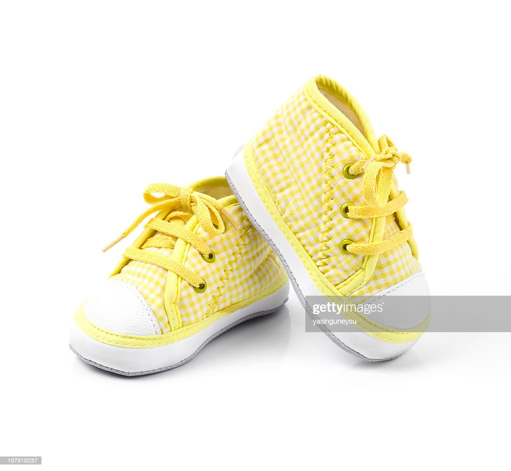 Cute yellow baby shoes with laces : Stock Photo