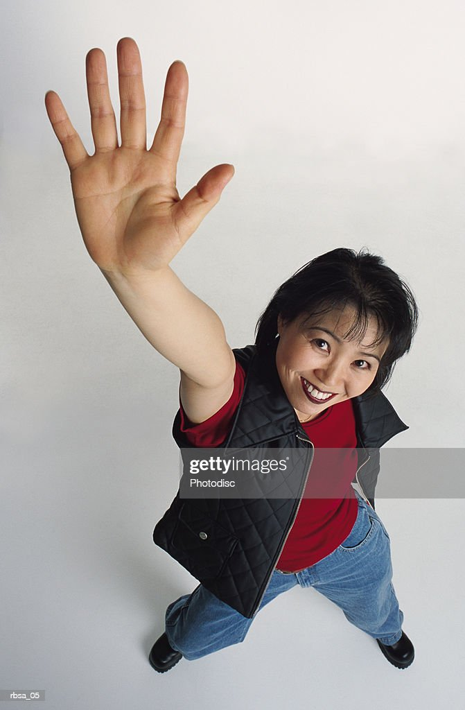 cute young adult asian female wears dark vest jeans stands hand raised looks to camera smiles play : Foto de stock