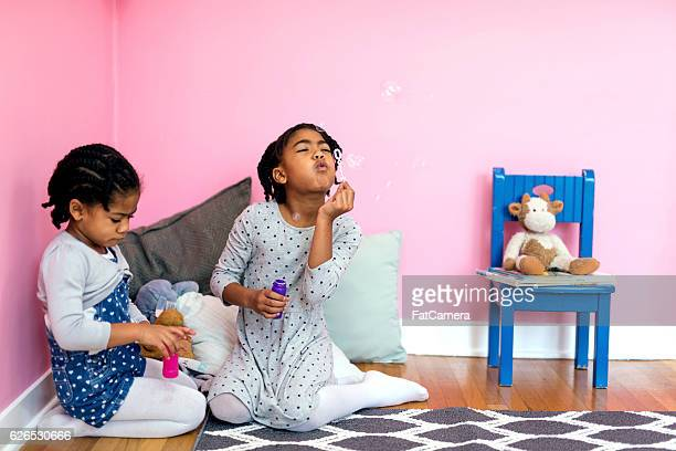 Cute young African American sisters blowing bubbles inside pink bedroom