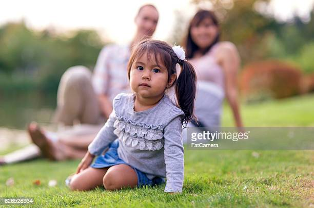 Cute young Asian girl sitting in front of her parents