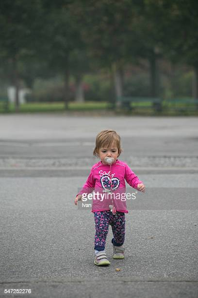 A Cute Young Baby Learning to Walk With Pacifier