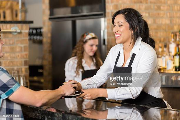 cute young barista serving latte in local coffee shop - coffee drink stock pictures, royalty-free photos & images