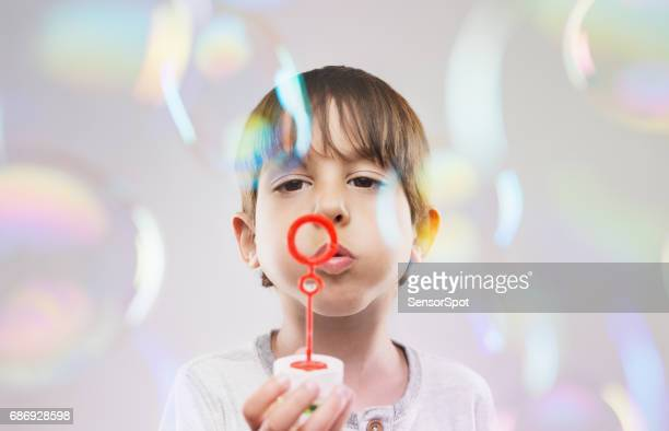 Cute young boy blowing soap bubble