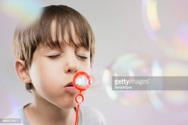 Cute young boy blowing soap bubbles