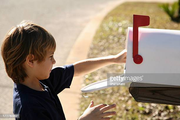 Cute young boy drops off mail in mailbox