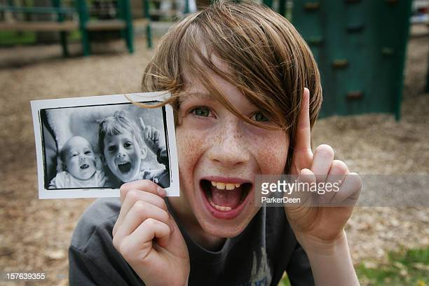 Cute Young Boy Holding Up Photo of Himself When Younger