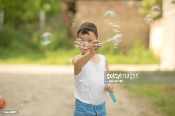 Cute young boy making bubbles with a bubble wand