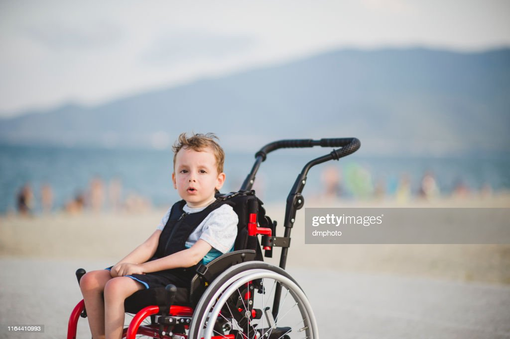 Cute young boy on the wheelchair by the sea : Stock Photo