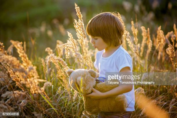 Cute young boy, playing with teddy bear in a field on sunset, summertime