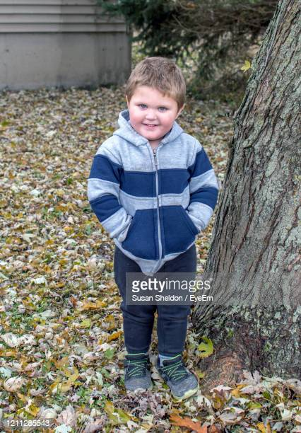 a cute young boy stands outdoors with hands in the pockets of his hooded jacket - by sheldon levis fotografías e imágenes de stock