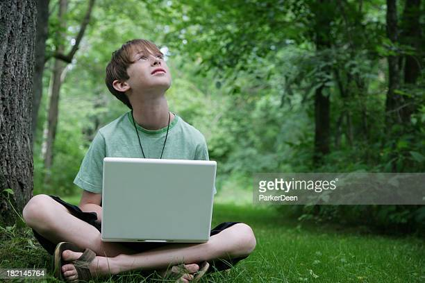 Cute Young Boy Using Computer in Nature