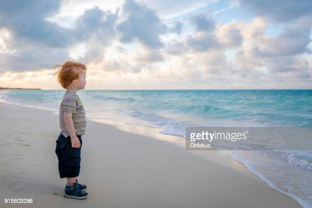 Cute Young Boy Walking on Beach