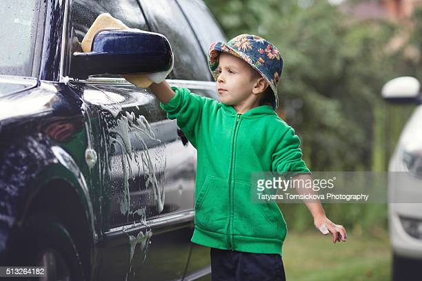Cute young boy washing car with sponge in a garden, summertime
