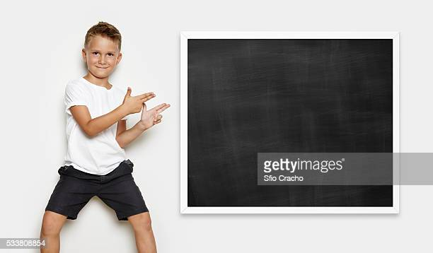 cute young boy wearing white t-shirt points on a school chalkboard - white shirt stock pictures, royalty-free photos & images