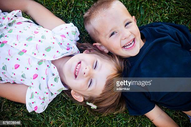 cute young children smiling on grass - nice girls pic stock photos and pictures