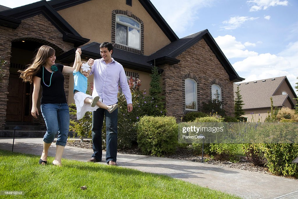 Cute Young Couple and Child with Beautiful Home : Stock Photo