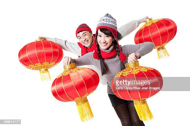 Cute young couple celebrating Chinese New Year with red lanterns