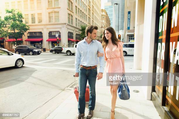 a cute young couple with their luggage walks side by side on a footpath in dallas. - casal heterossexual - fotografias e filmes do acervo